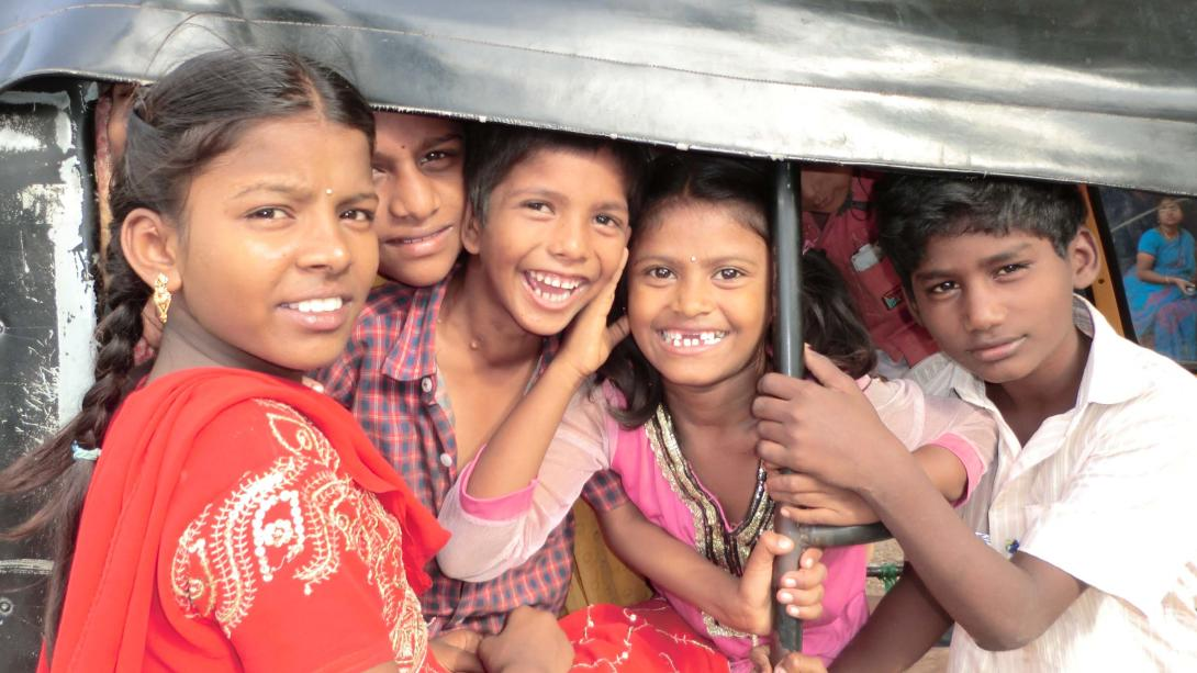 Local children smile from a tuk tuk in India.
